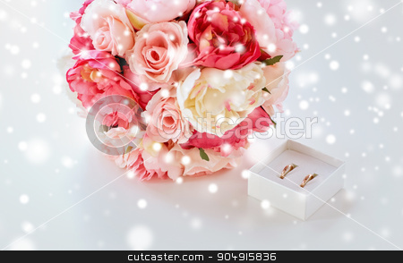 close up of gay wedding rings and flower bunch stock photo, people, homosexuality, same-sex marriage and love concept - close up of gay female wedding rings in little box and flower bunch on table over snow effect by Syda Productions
