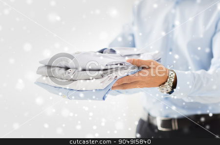 close up of businessman holding folded shirts stock photo, business, clothing and people concept - close up of businessman holding folded shirts over snow effect by Syda Productions