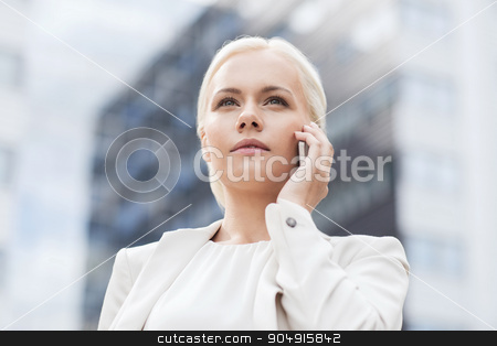 serious businesswoman with smartphone outdoors stock photo, business, technology and people concept - serious businesswoman with smartphone talking over office building by Syda Productions