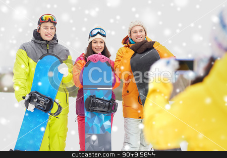 happy friends with snowboards and smartphone stock photo, winter sport, technology, leisure, friendship and people concept - happy friends with snowboards and smartphone taking picture outdoors by Syda Productions