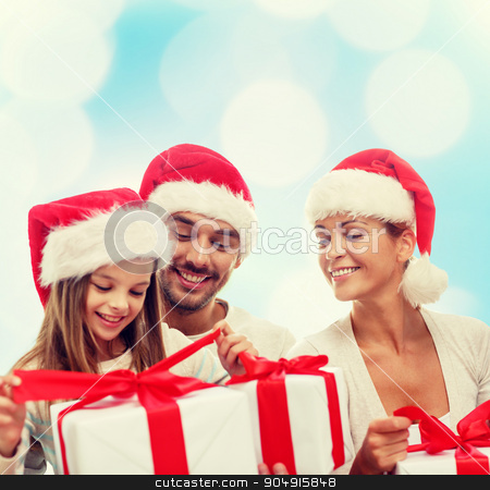 happy family in santa helper hats with gift boxes stock photo, family, christmas, generation, holidays and people concept - happy family in santa helper hats with gift boxes sitting over blue lights background by Syda Productions