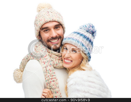 smiling couple in winter clothes hugging stock photo, winter, fashion, couple, christmas and people concept - smiling man and woman in hats and scarf hugging by Syda Productions