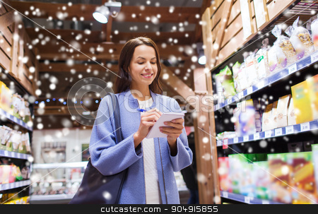 happy woman with notepad in market stock photo, sale, shopping, consumerism and people concept - happy young woman taking notes to notebook in market over snow effect by Syda Productions