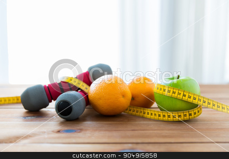 close up of dumbbell, fruits and measuring tape stock photo, sport, fitness, diet and objects concept - close up of dumbbell and green apple with oranges wrapped by measuring tape on wooden table by Syda Productions