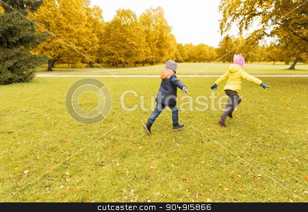 group of happy little kids running outdoors stock photo, autumn, childhood, leisure and people concept - group of happy little kids playing tag game and running in park outdoors by Syda Productions