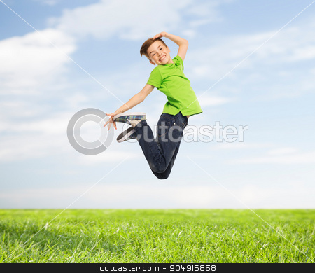 smiling boy jumping in air stock photo, happiness, childhood, freedom, movement and people concept - smiling boy jumping in air over blue sky and grass background by Syda Productions