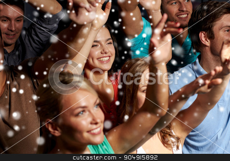 smiling friends at concert in club stock photo, party, holidays, celebration, nightlife and people concept - smiling friends waving hands at concert in club and snow effect by Syda Productions