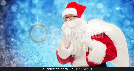 man in costume of santa claus with bag stock photo, christmas, holidays and people concept - man in costume of santa claus with bag making hush gesture over blue glitter or lights background by Syda Productions