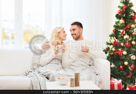 happy couple at home with christmas tree stock photo, family, christmas, holidays, love and people concept - happy couple covered with plaid drinking tea and sitting on sofa at home by Syda Productions
