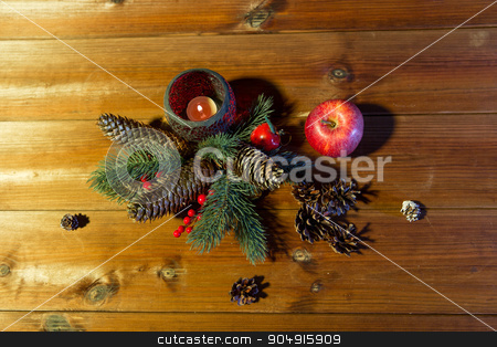 christmas fir branch decoration and candle lantern stock photo, christmas, decoration, holidays and new year concept - close up of natural fir branch decoration and fir-cone and candle in lantern on wooden table by Syda Productions
