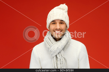 handsome man in warm sweater, hat and scarf stock photo, people, christmas, fashion, season and clothing concept - handsome man in winter wear over red background by Syda Productions