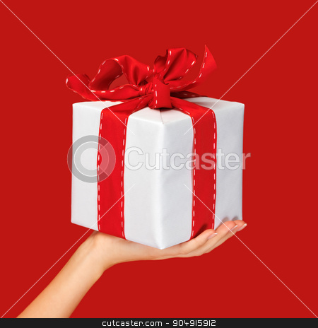 close up hand holding christmas gift box over red stock photo, people, holidays, present, surprise and birthday concept - close up hand holding christmas gift box over red background by Syda Productions