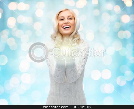 woman in winter earmuffs holding fairy dust stock photo, winter, magic, christmas and people concept - smiling young woman in earmuffs and sweater holding fairy dust on palms over blue holidays lights background by Syda Productions