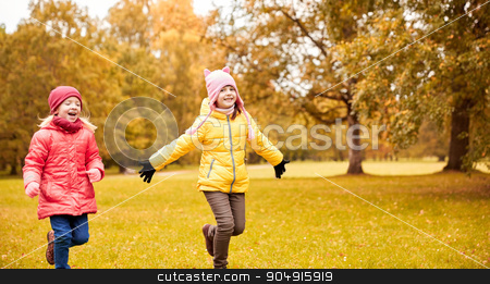 group of happy little girls running outdoors stock photo, autumn, childhood, leisure and people concept - happy little girls playing tag game and running in park outdoors by Syda Productions