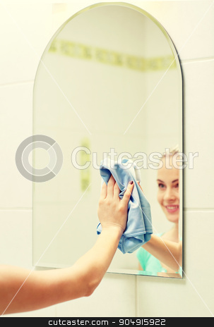 close up of happy woman cleaning mirror with rag stock photo, people, housework and housekeeping concept - close up of happy woman cleaning mirror with rag at home by Syda Productions