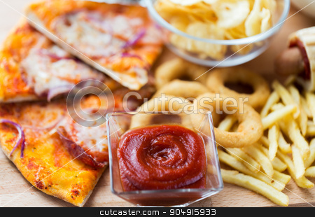 close up of fast food snacks on wooden table stock photo, fast food and unhealthy eating concept - close up of ketchup in glass bowl over pizza, deep-fried squid rings, potato chips, peanuts and ketchup on wooden table by Syda Productions