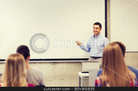 group of students and smiling teacher in classroom stock photo, education, high school, technology and people concept - smiling teacher standing with remote control, laptop computer in front of white board and students in classroom by Syda Productions
