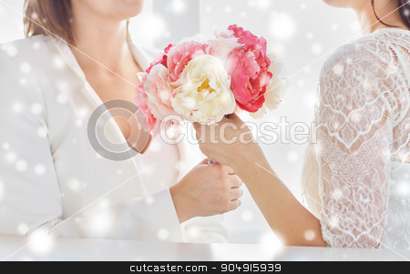 close up of happy lesbian couple with flowers stock photo, people, homosexuality, same-sex marriage and love concept - close up of happy married lesbian couple with flower bunch over snow effect by Syda Productions
