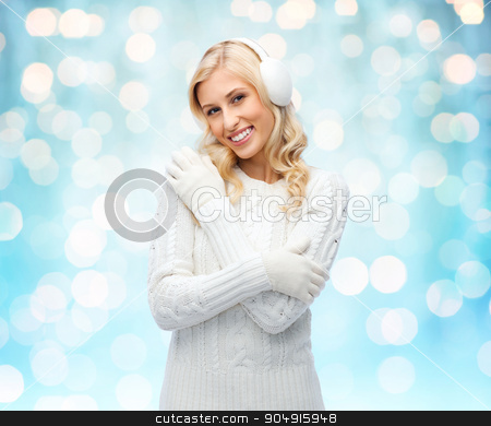 smiling young woman in winter earmuffs and sweater stock photo, winter, fashion, christmas and people concept - smiling young woman in earmuffs and sweater over blue holidays lights background by Syda Productions