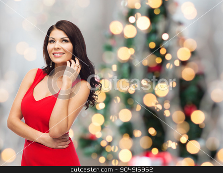 beautiful sexy woman in red over christmas lights stock photo, people, christmas, holidays and luxury concept - beautiful sexy woman in red dress over lights background by Syda Productions