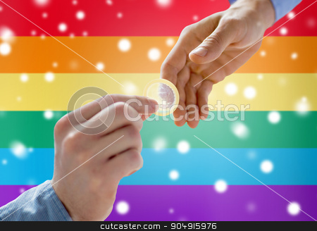 close up of male gay couple hands giving condom stock photo, people, homosexuality, safe sex, sexual education and charity concept - close up of happy male gay couple hands giving condom over rainbow flag background and snow effect by Syda Productions