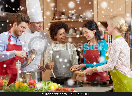 happy friends and chef cook cooking in kitchen stock photo, cooking class, culinary, food and people concept - happy group of friends and male chef cook cooking in kitchen over snow effect by Syda Productions
