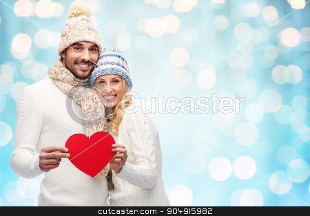 smiling couple in winter clothes with red hearts stock photo, love, valentines day, couple, christmas and people concept - smiling man and woman in winter hats and scarf holding red paper heart shape over blue holidays lights background by Syda Productions