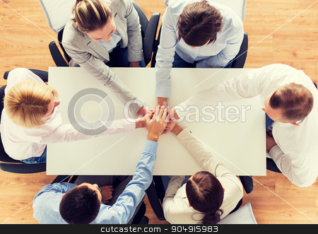 close up of business team with hands on top stock photo, business, people, cooperation and team work concept - close up of creative team sitting at table and holding hands on top of each other in office by Syda Productions