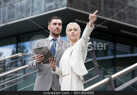 serious businessmen with tablet pc outdoors stock photo, business, partnership, technology and people concept - serious businessman and businesswoman with tablet pc computer over office building by Syda Productions