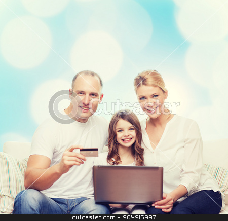 happy family with laptop computer and credit card stock photo, family, holidays, shopping, technology and people concept - happy family with laptop computer and credit card over blue lights background by Syda Productions