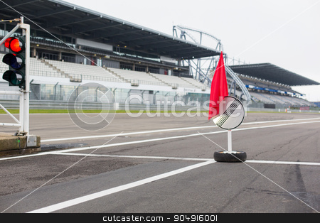 red traffic lights and road sign on race track stock photo, motosports, extreme and race concept - close up of red traffic lights and road sign with flag on speedway track or road by Syda Productions