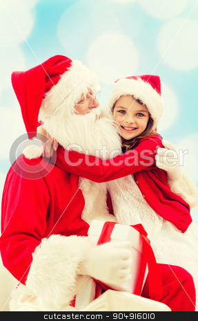 smiling little girl with santa claus stock photo, holidays, christmas, childhood and people concept - smiling little girl hugging with santa claus over blue lights background by Syda Productions