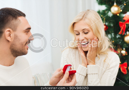 man giving woman engagement ring for christmas stock photo, love, christmas, couple, proposal and people concept - happy man giving diamond engagement ring in little red box to woman at home by Syda Productions