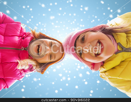 happy little girls faces over blue sky and snow stock photo, childhood, friendship, christmas, winter and people concept - happy little girls faces outdoors over blue sky and snow background by Syda Productions