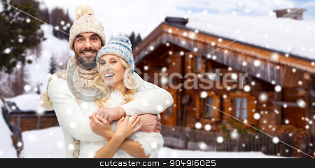 smiling couple in winter clothes hugging outdoors stock photo, winter, vacation, couple, christmas and people concept - smiling man and woman in hats and scarf hugging over wooden country house and snow background by Syda Productions