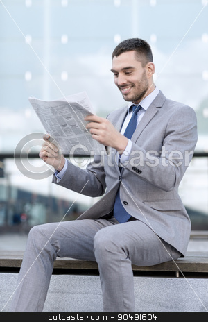 young smiling businessman newspaper outdoors stock photo, business, hot drinks and people and concept - young smiling businessman with newspaper over office building by Syda Productions