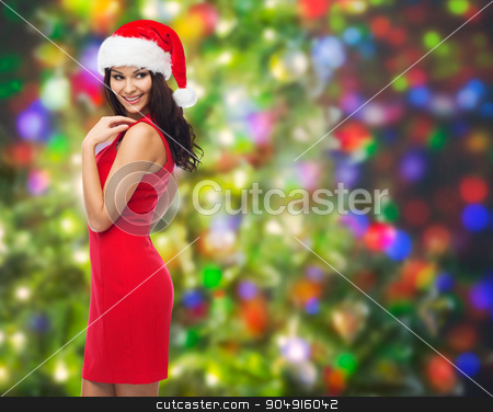 beautiful sexy woman in santa hat and red dress stock photo, people, holidays, christmas and celebration concept - beautiful sexy woman in santa hat and red dress over party lights background by Syda Productions