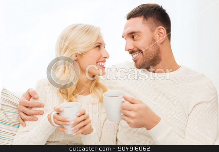 happy couple with cups drinking tea at home stock photo, family, winter, holidays, love and people concept - happy couple with cups drinking tea and sitting on sofa at home by Syda Productions