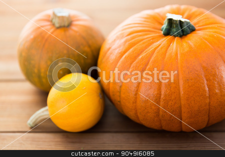 close up of pumpkins on wooden table at home stock photo, food, harvest, season and autumn concept - close up of pumpkins on wooden table at home by Syda Productions