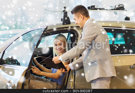 happy woman with car dealer in auto show or salon stock photo, auto business, car sale, consumerism and people concept - happy woman with car dealer in auto show or salon over snow effect by Syda Productions