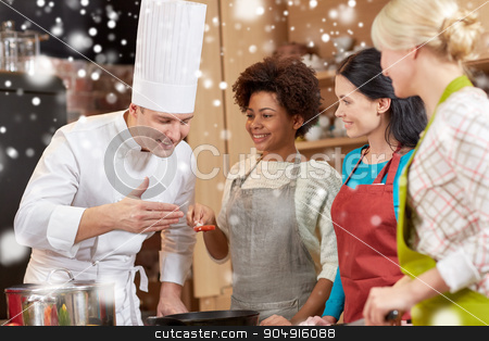 happy women and chef cook cooking in kitchen stock photo, cooking class, culinary, food and people concept - happy group of women and male chef cook cooking in kitchen over snow effect by Syda Productions