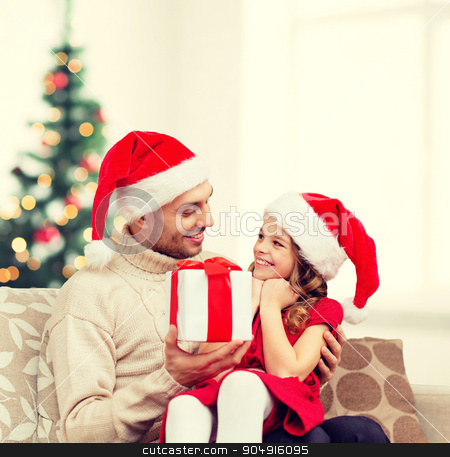 smiling father giving daughter gift box stock photo, family, christmas, x-mas, winter, happiness and people concept - smiling father giving daughter gift box by Syda Productions