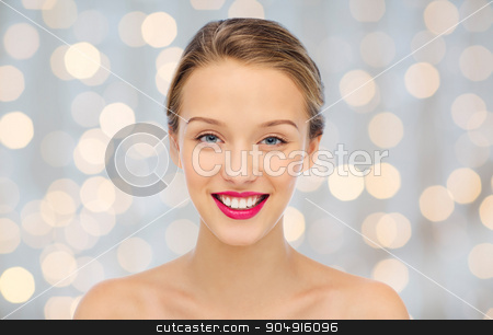 smiling young woman face and shoulders stock photo, beauty, people and health concept - smiling young woman face with pink lipstick on lips and shoulders over holidays lights background by Syda Productions