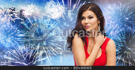 beautiful woman in red over firework at night city stock photo, people, holidays and fashion concept - beautiful sexy woman in red dress over firework in night city background by Syda Productions
