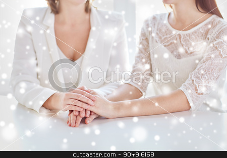 close up of happy married lesbian couple hands stock photo, people, homosexuality, same-sex marriage and love concept - close up of happy married lesbian couple hands over snow effect by Syda Productions