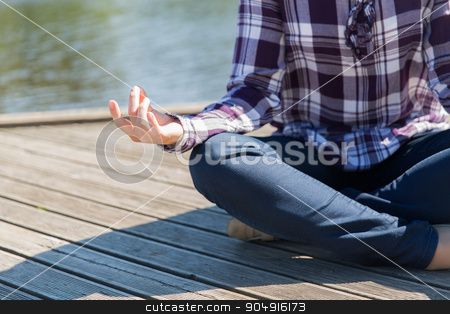 close up of woman in yoga lotus pose outdoors stock photo, yoga, meditation, people and lifestyle concept - close up of woman meditating in lotus pose outdoors on berth by Syda Productions