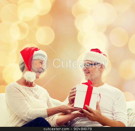 happy senior couple with gift box at home stock photo, family, holidays, christmas, age and people concept - happy senior couple with gift box over beige lights background by Syda Productions