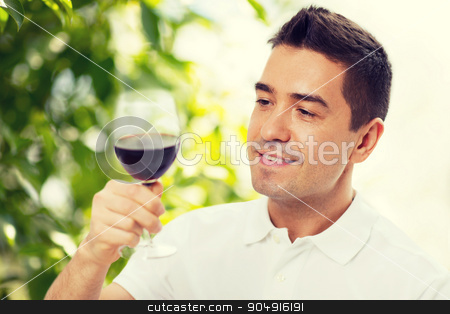 happy man drinking red wine from glass stock photo, profession, drinks, leisure, holidays and people concept - happy man drinking red wine from glass over green background by Syda Productions