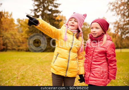 happy little girls pointing finger in autumn park stock photo, autumn, childhood, leisure, gesture and people concept - happy little girls pointing finger in park outdoors by Syda Productions