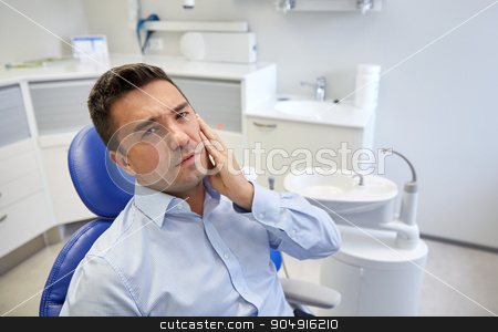 man having toothache and sitting on dental chair stock photo, people, medicine, stomatology and health care concept - unhappy male patient having toothache sitting on dental chair at clinic office by Syda Productions